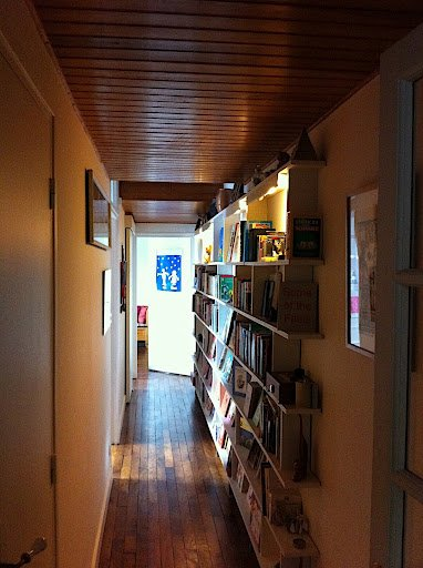 long-hallway-with-dark-wood-ceiling-and-jammed-with-books