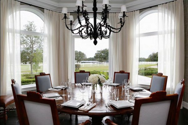 Interesting-dining-room-with-curving-windows-and-green-view-and-wooden-round-table-and-antique-chandelier-and-glass-cup-and-plate
