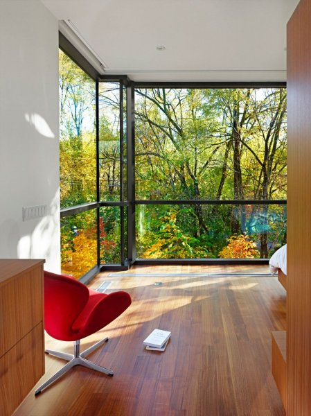 Red-Chair-Overlooking-Green-Outside-View-Through-Glass-Wall