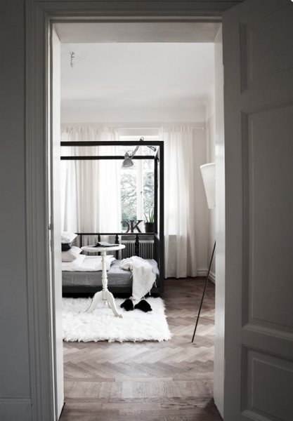 Casual-Nordic-Interior-In-Black-White-And-Grey-with-wooden-door-bed-pillow-blanket-carpet-table-lamp-window-curtain-hardwood-floor